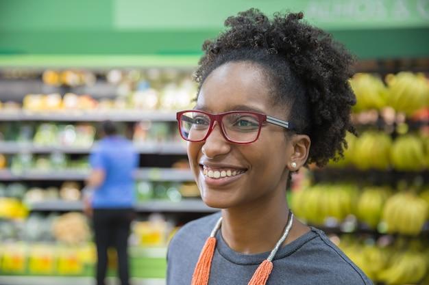Bela jovem negra sorrindo em um supermercado