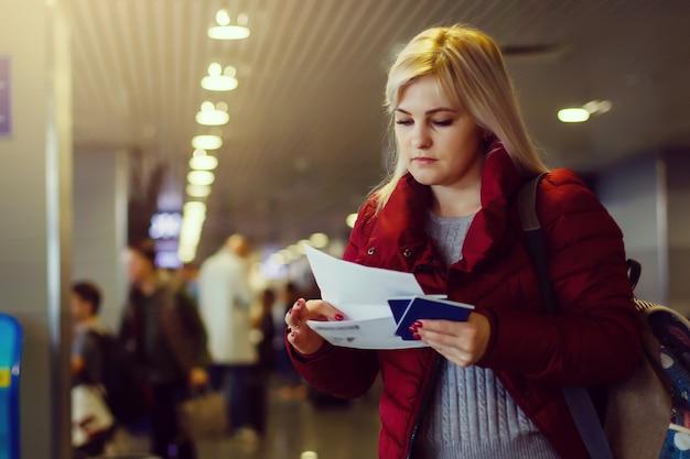Bela jovem no aeroporto com bilhetes e passaportes