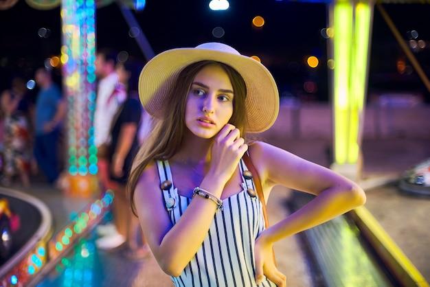 Bela jovem no contexto de luzes mágicas carrossel brilhante.