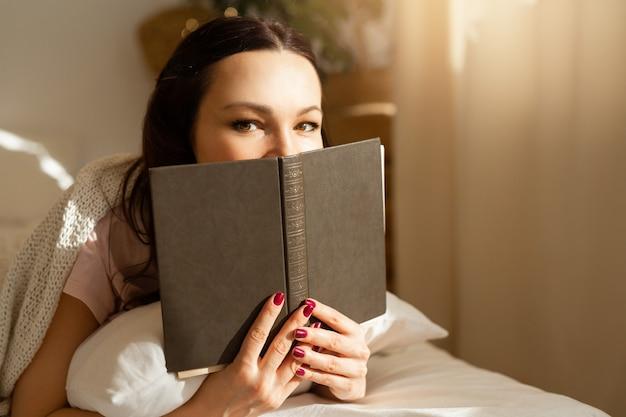 Bela jovem no quarto na cama com um livro