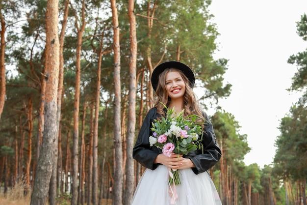 Bela jovem noiva com buquê de flores no dia do casamento ao ar livre
