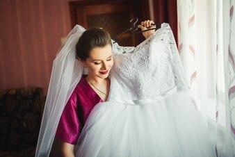 Bela jovem noiva com casamento maquiagem e penteado no quarto