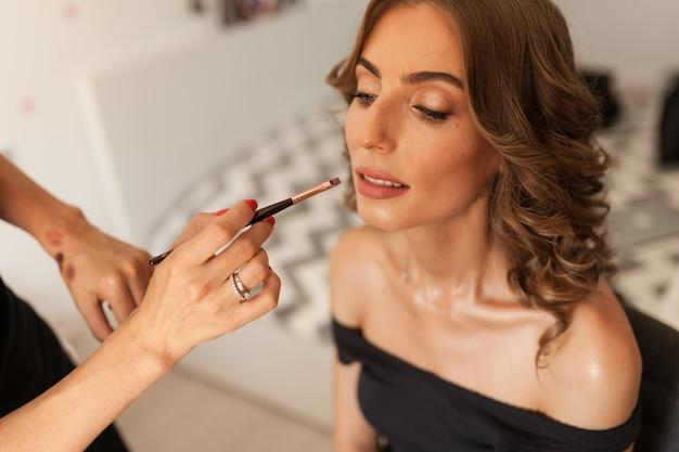 Bela jovem noiva com maquiagem de casamento e penteado