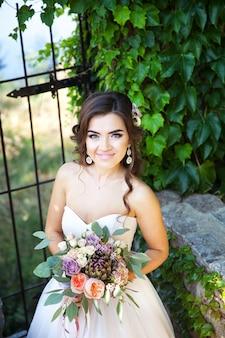 Bela jovem noiva com um buquê de flores do casamento.