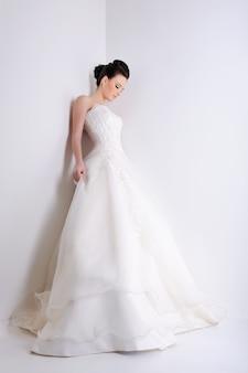 Bela jovem noiva com um elegante vestido de noiva branco