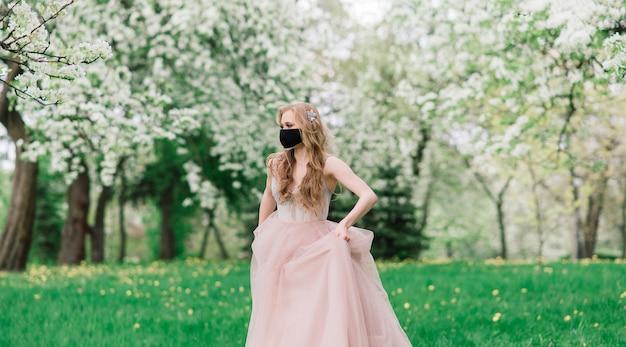 Bela jovem noiva em um vestido de noiva e uma máscara médica preta no rosto perto de uma macieira florescendo. proteção contra o covid19.