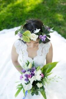 Bela jovem noiva em uma coroa de flores com um buquê na mão