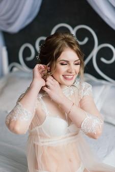 Bela jovem noiva em uma lingerie branca. últimos preparativos para o casamento à espera do noivo.