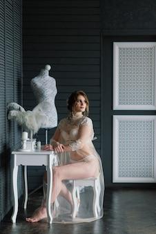 Bela jovem noiva em uma lingerie branca. últimos preparativos para o casamento. a garota está esperando o noivo.
