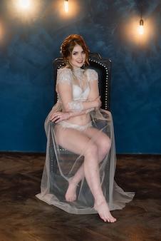 Bela jovem noiva em uma lingerie branca. últimos preparativos para o casamento. a menina está esperando o noivo.
