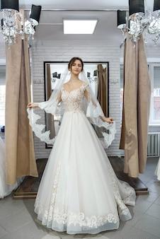 Bela jovem noiva posando em vestido de noiva em salão
