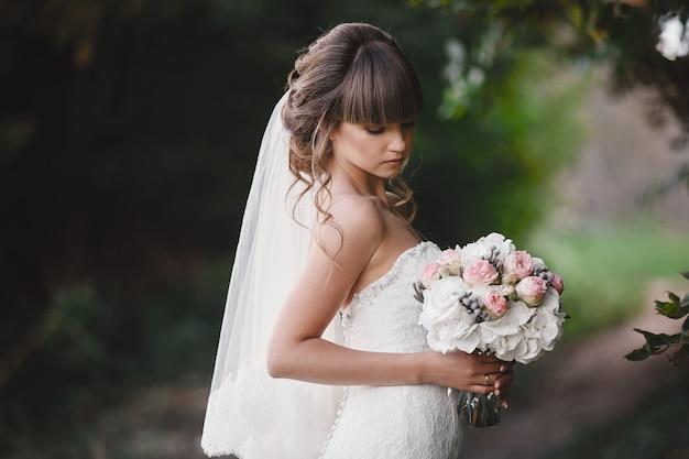 Bela jovem noiva sorridente detém buquê de casamento grande com rosas. casamento em tons de rosa e verde. dia do casamento.