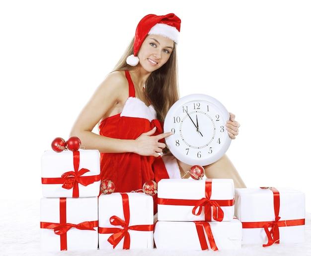Bela jovem num terno de natal com um relógio sentado sobre as caixas com os presentes de natal. .