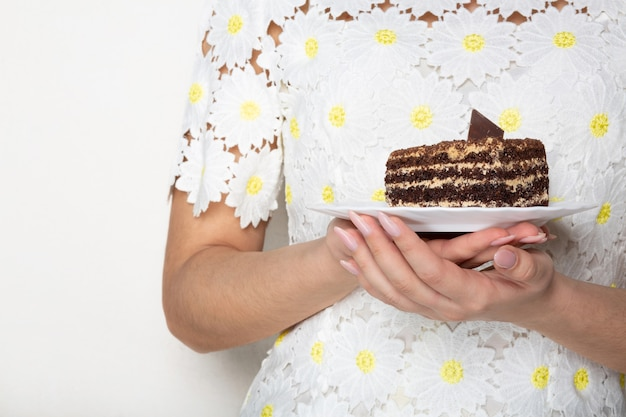 Bela jovem num vestido elegante, segurando um prato com saboroso bolo de chocolate. espaço vazio