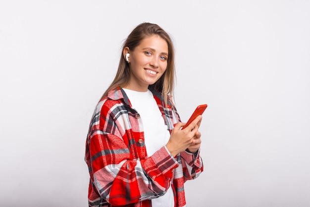Bela jovem olha para a câmera enquanto usa protetores de ouvido e segura seu telefone vermelho.