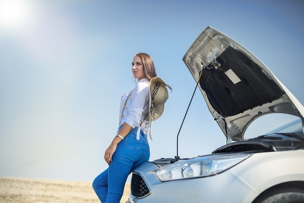 Bela jovem olhando para o motor de um carro quebrado. problemas de viagem.