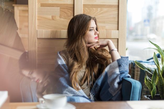 Bela jovem olhando pela janela