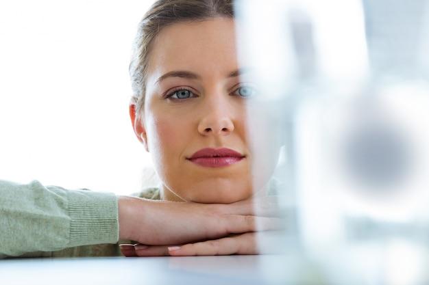 Bela jovem olhando um copo com uma pílula efervescente.