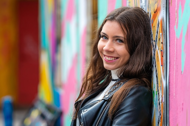 Bela jovem parada perto da parede pintada com pichações