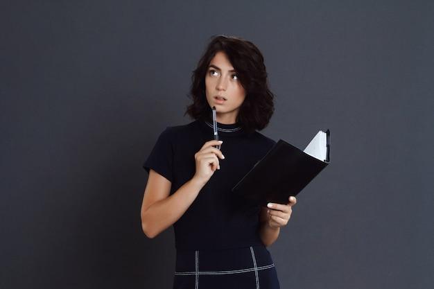 Bela jovem pensativa posando sobre parede cinza e segurando o caderno nas mãos