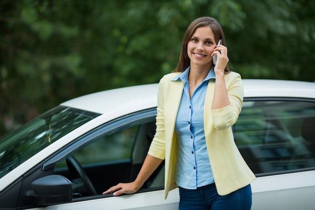 Bela jovem perto do carro com um telefone celular
