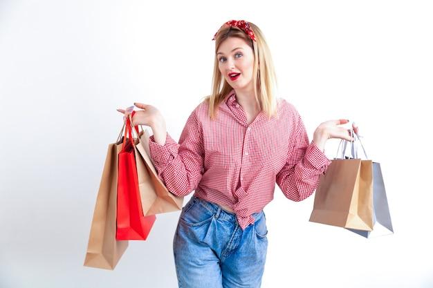 Bela jovem pin-up de camisa quadriculada e bandana segurando sacolas de compras no fundo da parede branca.