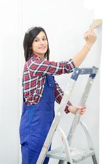 Bela jovem pinta a cor branca da parede