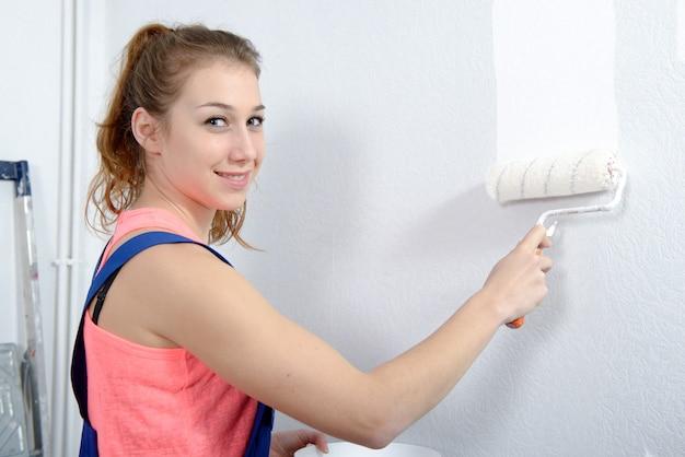 Bela jovem pintando a cor branca da parede