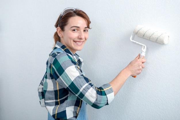 Bela jovem pintando a parede