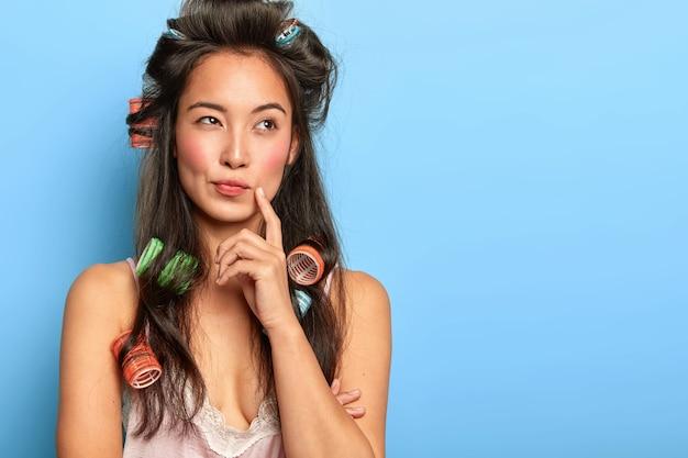 Bela jovem posando com rolos de cabelo