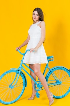 Bela jovem posando sentado em uma bicicleta azul