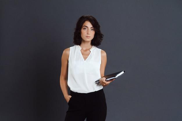Bela jovem posando sobre parede cinza e segurando o caderno nas mãos