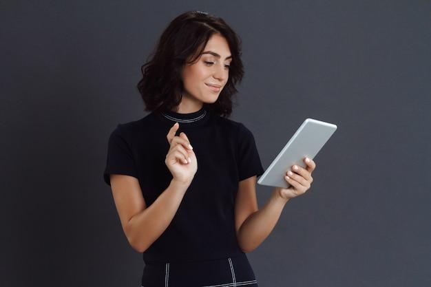 Bela jovem posando sobre parede cinza e segurando o tablet nas mãos