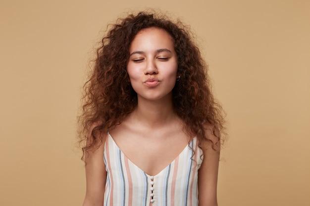 Bela jovem positiva encaracolada morena mantendo os olhos fechados enquanto franze os lábios no ar beijo, vestindo uma blusa casual em pé em bege