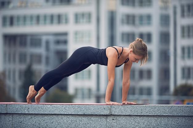 Bela jovem pratica yoga asana chaturanga dandasana - quatro membros com membros posam ao ar livre