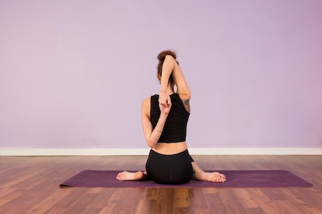 Bela jovem praticando ioga dentro de casa