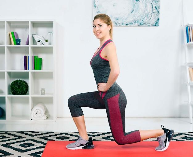 Bela jovem praticando ioga em casa