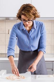 Bela jovem preparando a pizza na cozinha