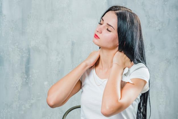 Bela jovem que sofre de dor no pescoço sentado contra a parede cinza