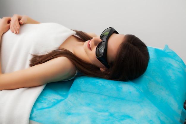 Bela jovem recebe depilação a laser para pernas no salão de beleza
