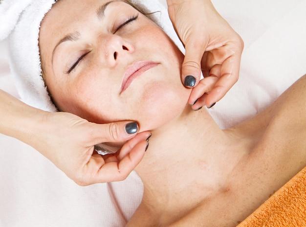 Bela jovem recebendo massagem facial com os olhos fechados em um centro de beleza