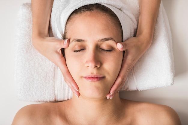 Bela jovem recebendo massagem facial com os olhos fechados em um salão de beleza spa