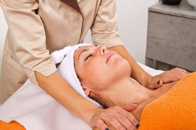 Bela jovem recebendo massagem facial com os olhos fechados