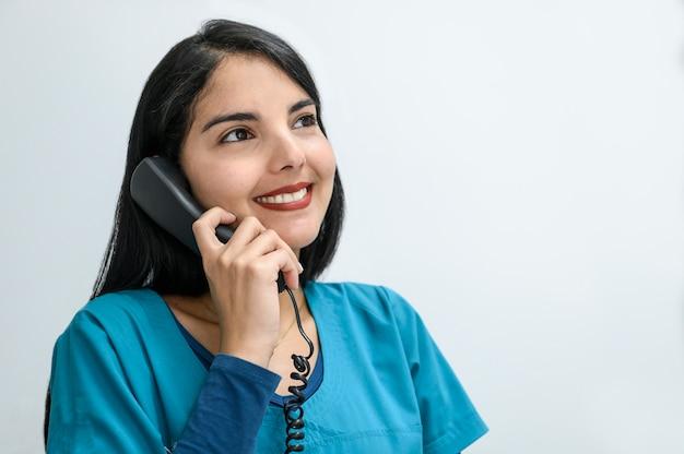 Bela jovem recepcionista está atendendo telefonemas.