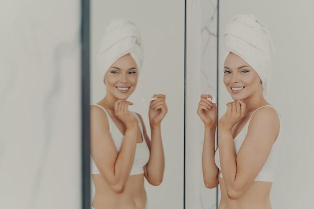 Bela jovem refletida no espelho fazendo a rotina matinal segura a escova de dentes enquanto escova os dentes no banheiro em casa, tratamento eficaz para dente branco saudável. conceito de higiene bucal pessoal