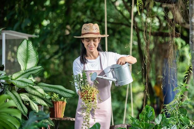 Bela jovem regando a árvore no jardim em um dia ensolarado de verão. mulher jardinagem fora na natureza de verão. conceito de agricultura, jardinagem, agricultura e pessoas.