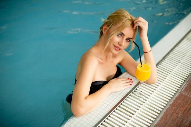 Bela jovem relaxando ao lado da piscina interna