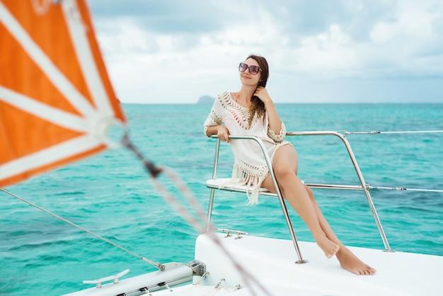 Bela jovem relaxando em um iate, aproveitando as férias de verão descuidadas