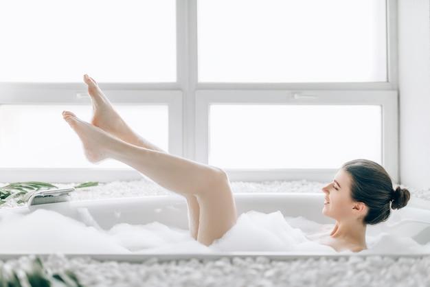 Bela jovem relaxando na banheira com espuma