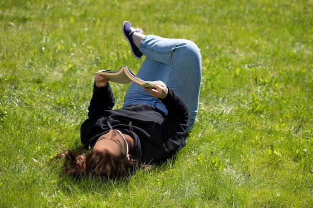Bela jovem relaxando na natureza lendo, deitada na grama verde